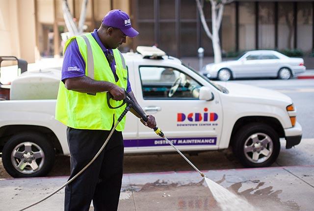 Man powerwashing sidewalk