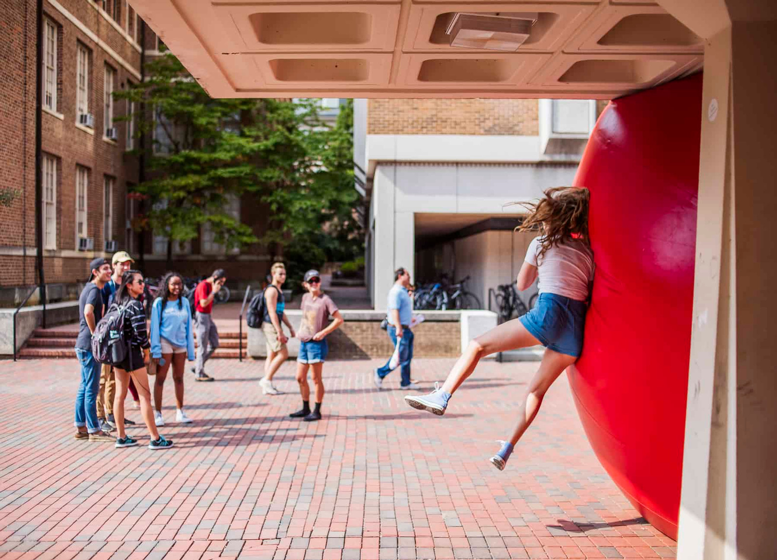 image of large red ball and a girl bouncing against it with a group watching, standing on a brick sidewalk