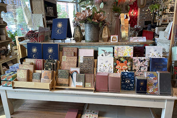 Various journals and notebooks with patterns on the covers are displayed on a wooden display