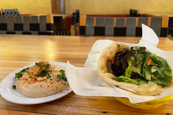 A photo of a lamb gyro and hummus on a table in a restaurant.