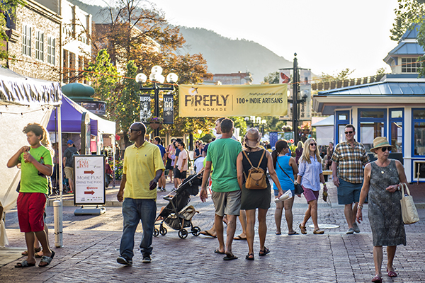 """People walking on an outdoor mall with a banner in the back reading """"Firefly Market"""""""