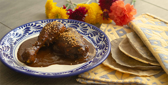 A plate of chicken covered in dark mole sauce.
