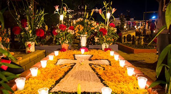 candle-lit, decorated gravesite in Oaxaca, Mexico