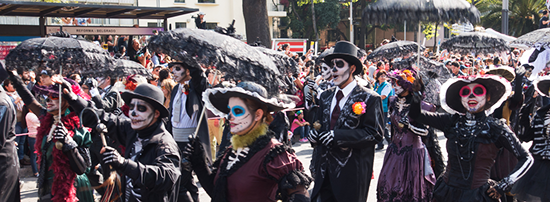 Parade participants march with skeleton facepaint through Mexico City
