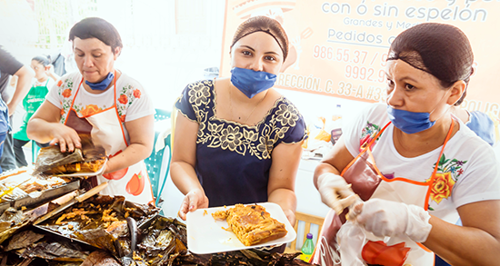 Three women serve traditional food in a park in Merida, Mexico