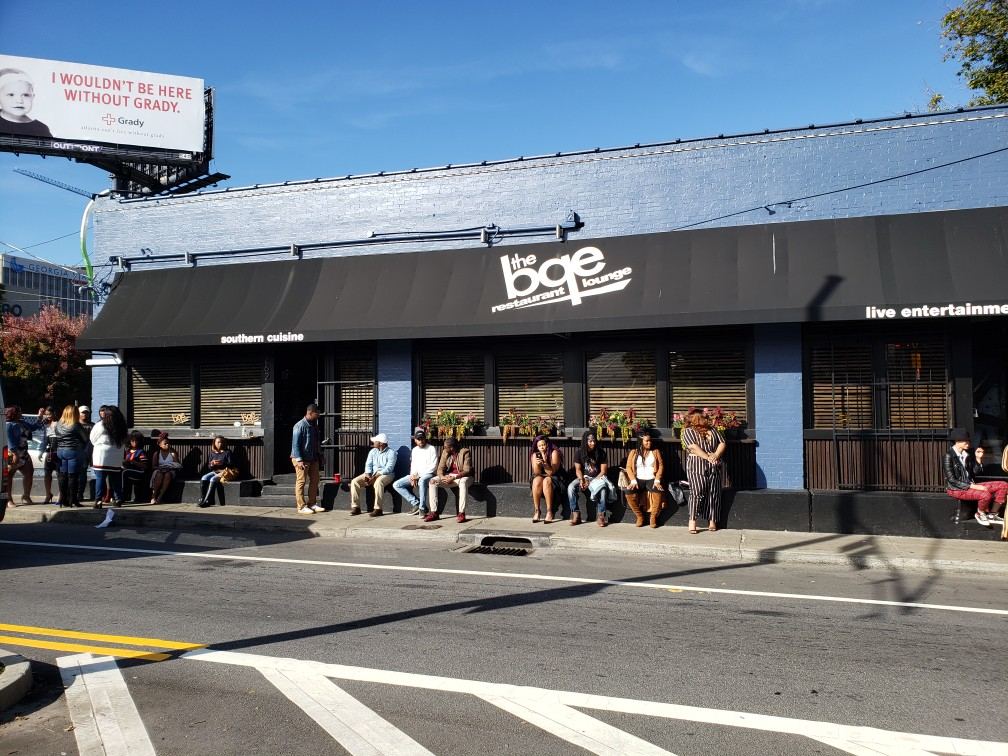 Image of building marquee of BQE Lounge with people sitting outside.