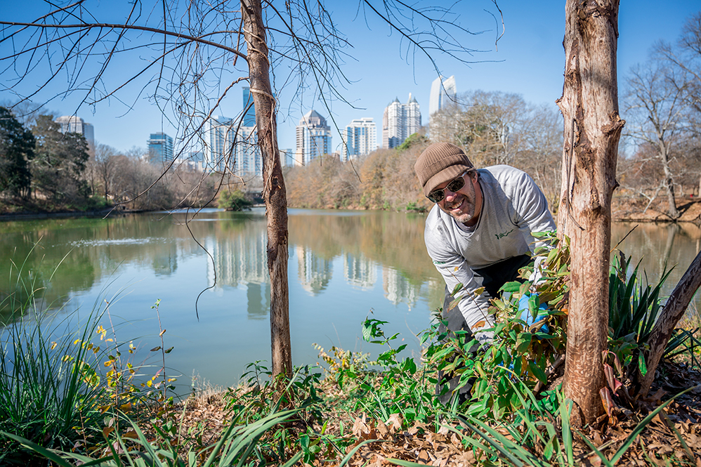 A member of the Piedmont Park Conservancy operations team landscaping along the edge of Lake Clara Meer, with the Midtown skyline in view behind him.