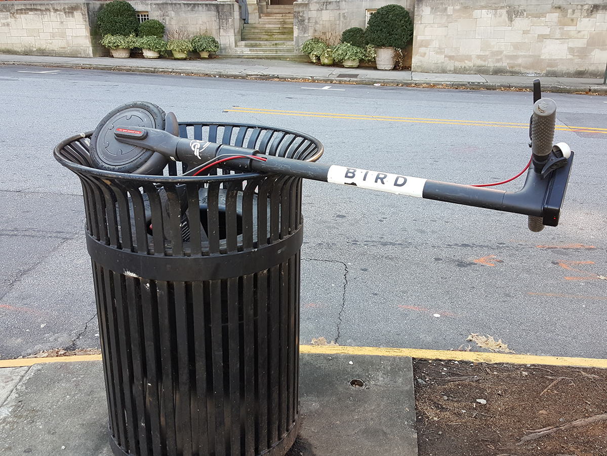 An image of a Bird Scooter discarded in a Midtown trashcan.