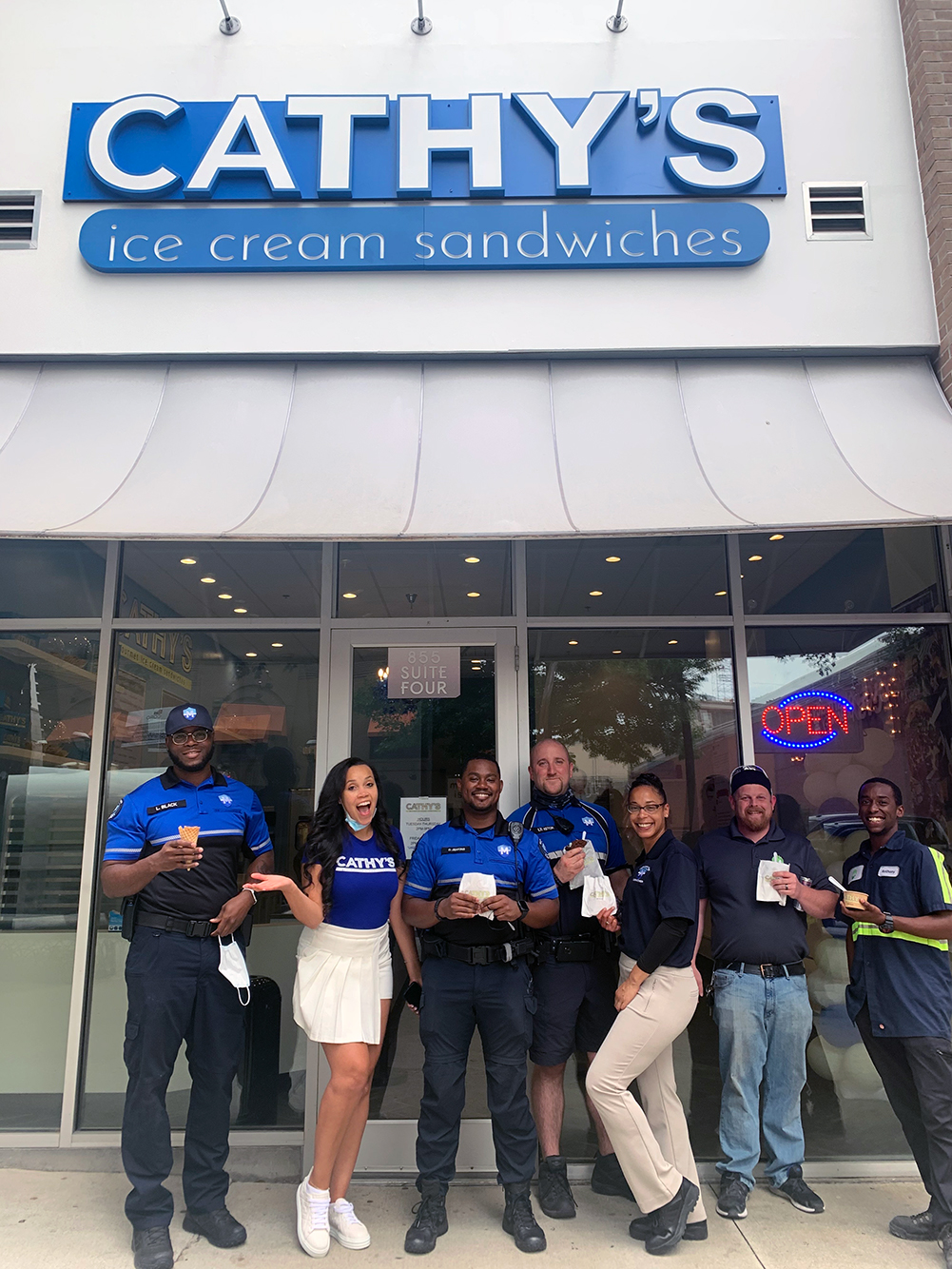 Cross (second from left) poses with members of Midtown's Blue and Green team outside her shop on Peachtree.