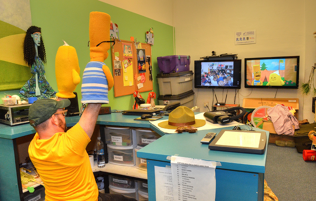 A puppeteer at the Center for Puppetry Arts performs an online show.
