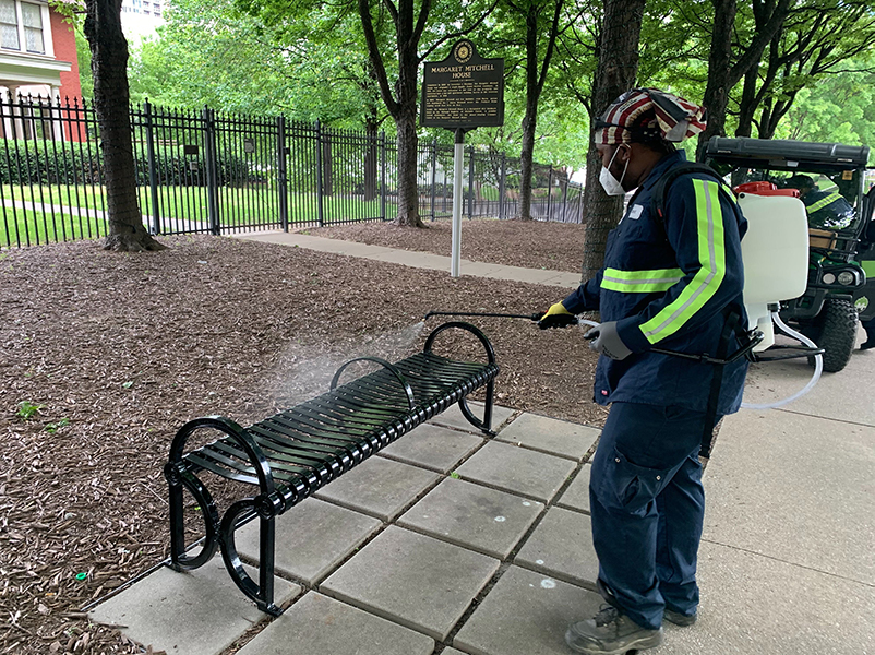 A Midtown Green staffer sanitizes a bench outside the Margaret Mitchell House