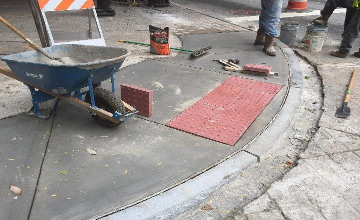 An image shows construction crews installing tactile, textured paving at a crosswalk.