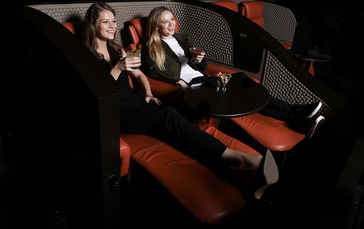 Theater with guests: Two guests enjoying a movie relaxing in IPIC's Premium Plus reclining leather seating Pods. Photo Credit: IPIC Theaters, LLC