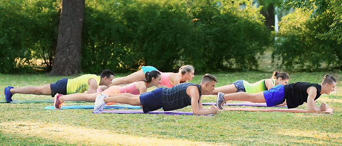 people doing yoga outdoors in a park