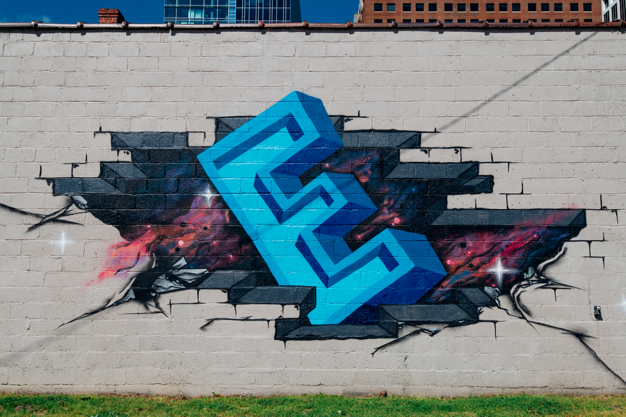 A blue, block letter capitalized E emerging from a galaxy