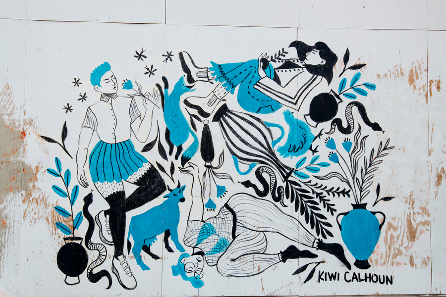 Three people in black, blue, and white clothing floating with pottery, snakes, a cow, a chicken, and a fox.
