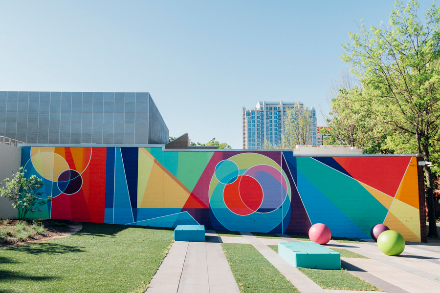 Mural on a brick wall with colorful geometric shapes