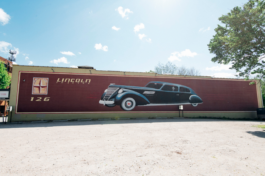 Mural on a brick wall depicting President Abraham Lincoln driving a 1950 Lincoln.