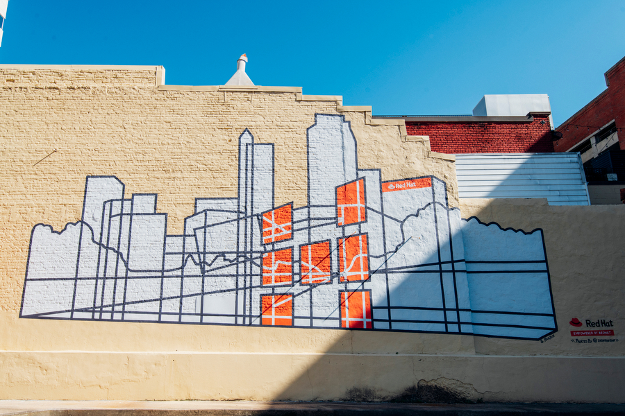 Mural featuring Raleigh's skyline in white and orange paint.