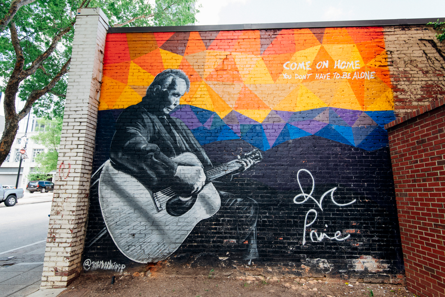 """Mural of musician John Prine playing a guitar with the lyrics """"Come on home you don't have to be alone"""""""