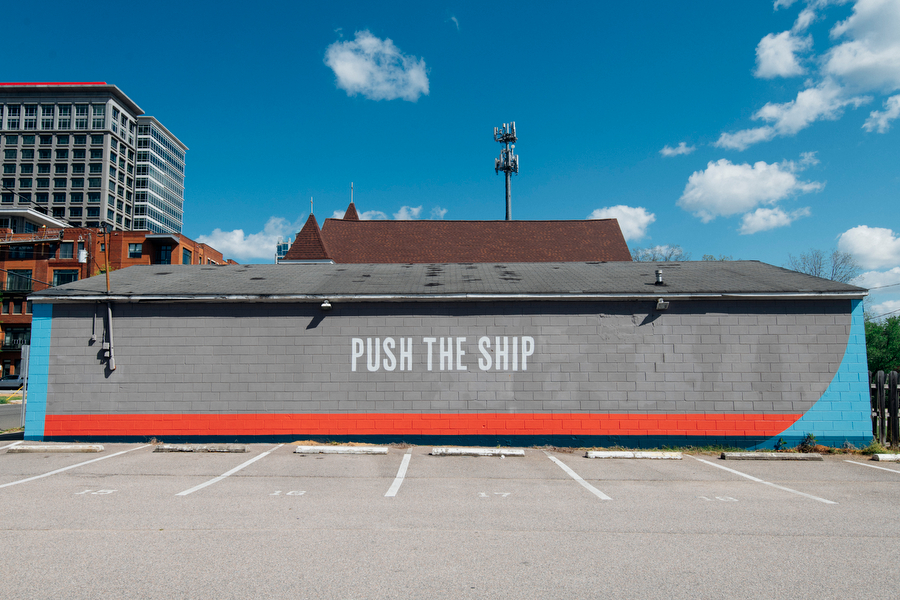 "Mural on gray wall with accents of red and blue and white capitalized letters reading ""Push The Ship""."