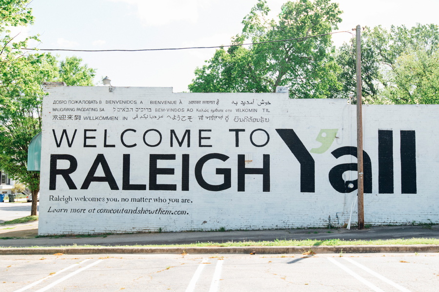"""Mural on brick wall with white background and black letters reading """"Welcome to Raleigh Y'all""""."""