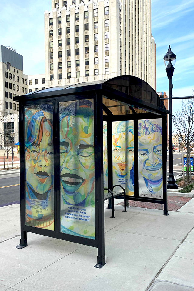 Photograph of downtown Akron, Main St. METRO RTA bus shelter with We Are artwork